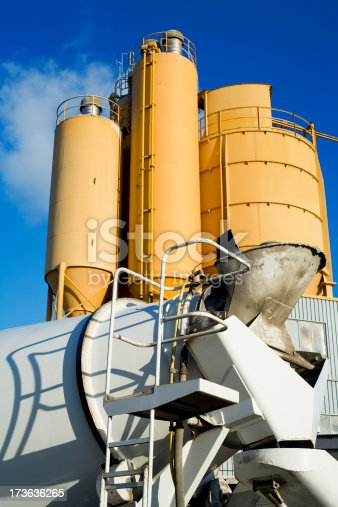 Yellow cement silos with cement mixer in the foreground