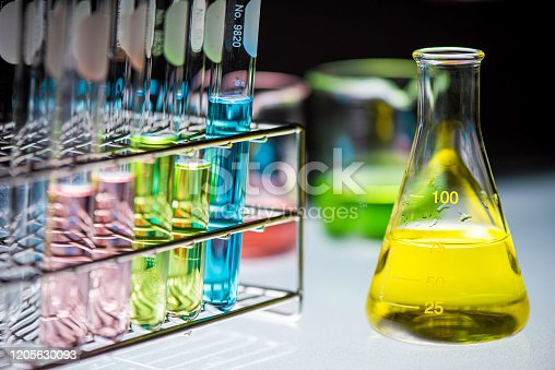 Yellow chemical liquid containing in flask with lab glassware on black background, la research and development concept.