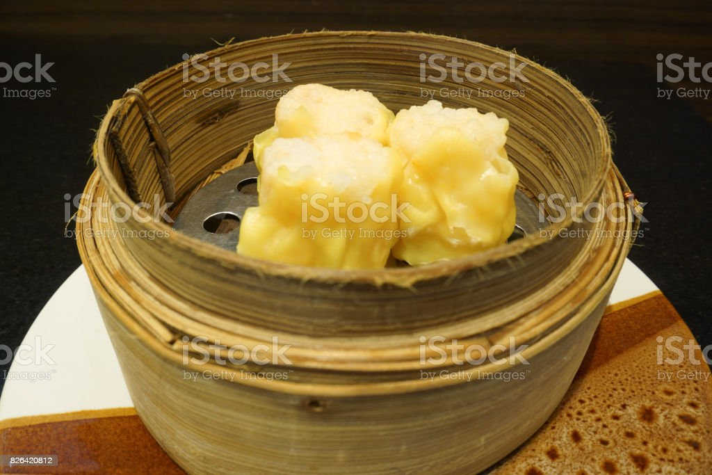 yellow Chinese dim sum dumpling and carrot on bamboo basket steamer stock photo