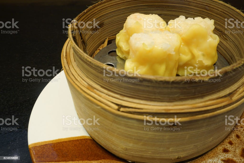 yellow Chinese dim sum dumpling on bamboo basket steamer, left copy space stock photo