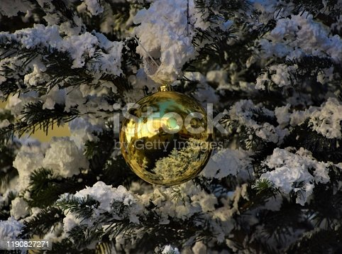 858960516 istock photo Yellow Christmas ball ornament on tree with fake snow detail 1190827271