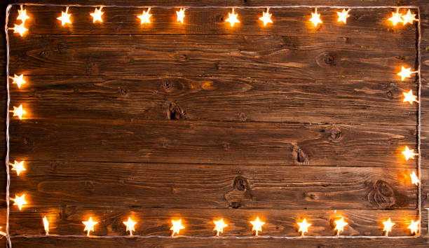 Yellow christmas light over rustic wooden background. Christmas or New Year concept stock photo