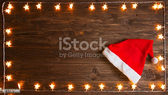 istock Yellow christmas light with Santa Claus hat over rustic wooden background. Christmas or New Year concept 871737586