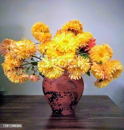 Yellow chrysanthemum flowers in an old ceramic vase. Earthen potting and yellow flowers.