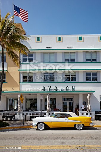 Miami, USA - February 13, 2020: Classic Oldsmobile with chrome radiator grill parks in front of the Hotel Avalon in Ocean Drive, Miami Beach, Florida, USA.