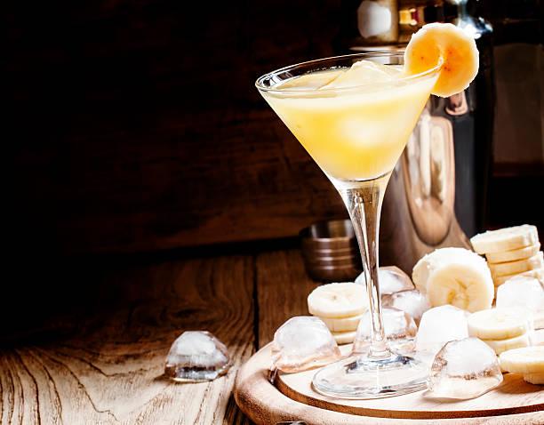 gelbe cocktail mit whiskey, banane und eis - bananenlikör stock-fotos und bilder