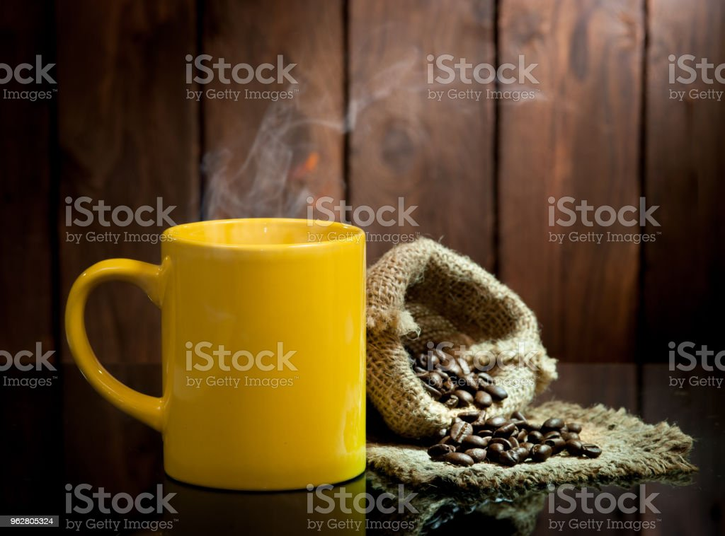 Yellow coffee cup and coffee beans on old wooden background. - Foto stock royalty-free di Arrosto - Cibo cotto