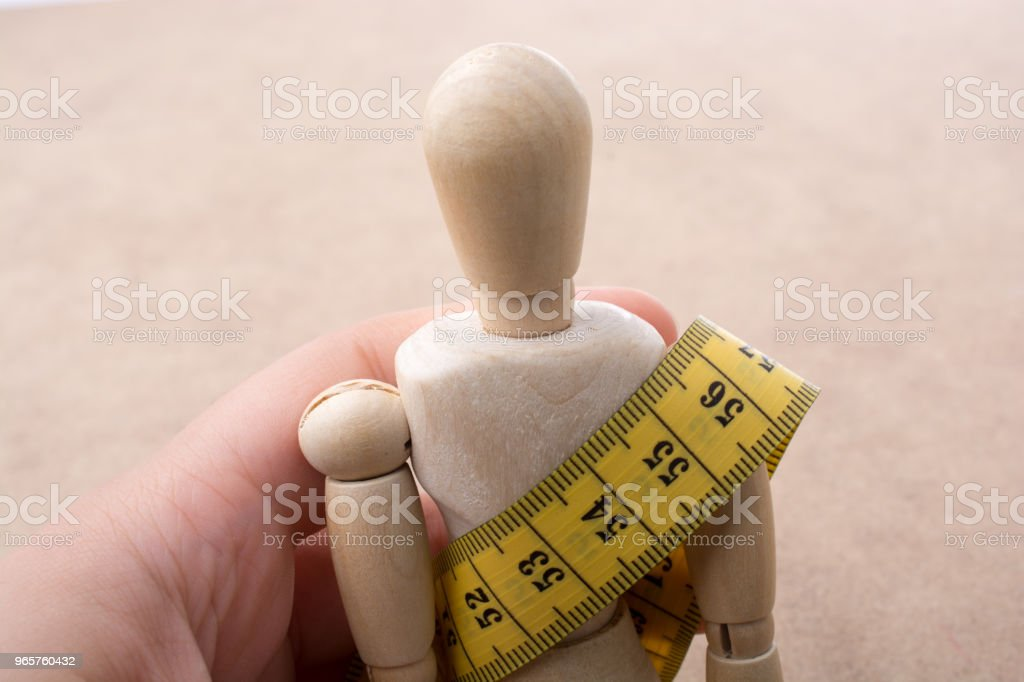 Yellow color measuring tape on wooden man - Royalty-free Accuracy Stock Photo