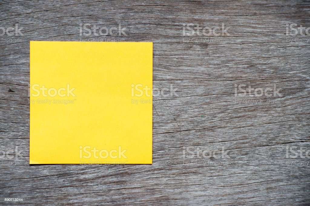 Yellow color paper attach on wood background for remind or memo stock photo