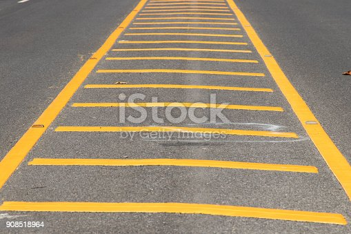 istock Yellow color road line on asphalt background 908518964