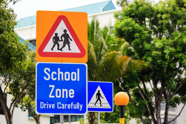 yellow color warning school zone traffic sign on road yellow color warning school zone traffic sign slow motion stock pictures, royalty-free photos & images
