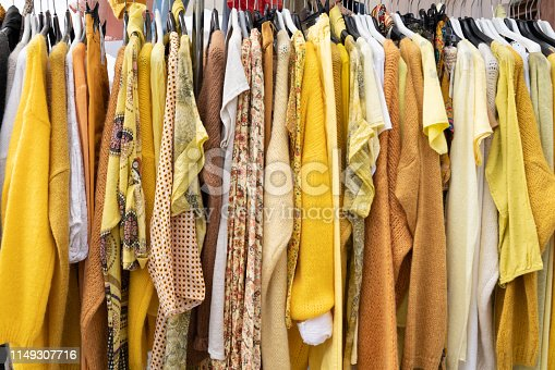 yellow woman clothes on hangers in store for background