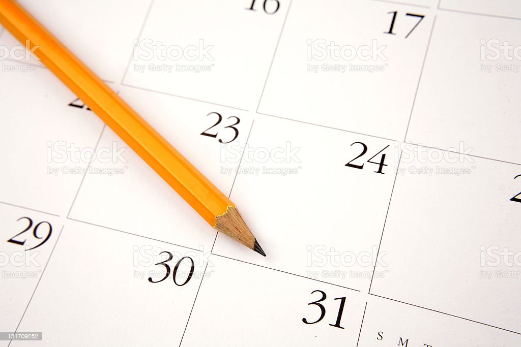 Yellow colored lead pencil rested on a calendar royalty-free stock photo