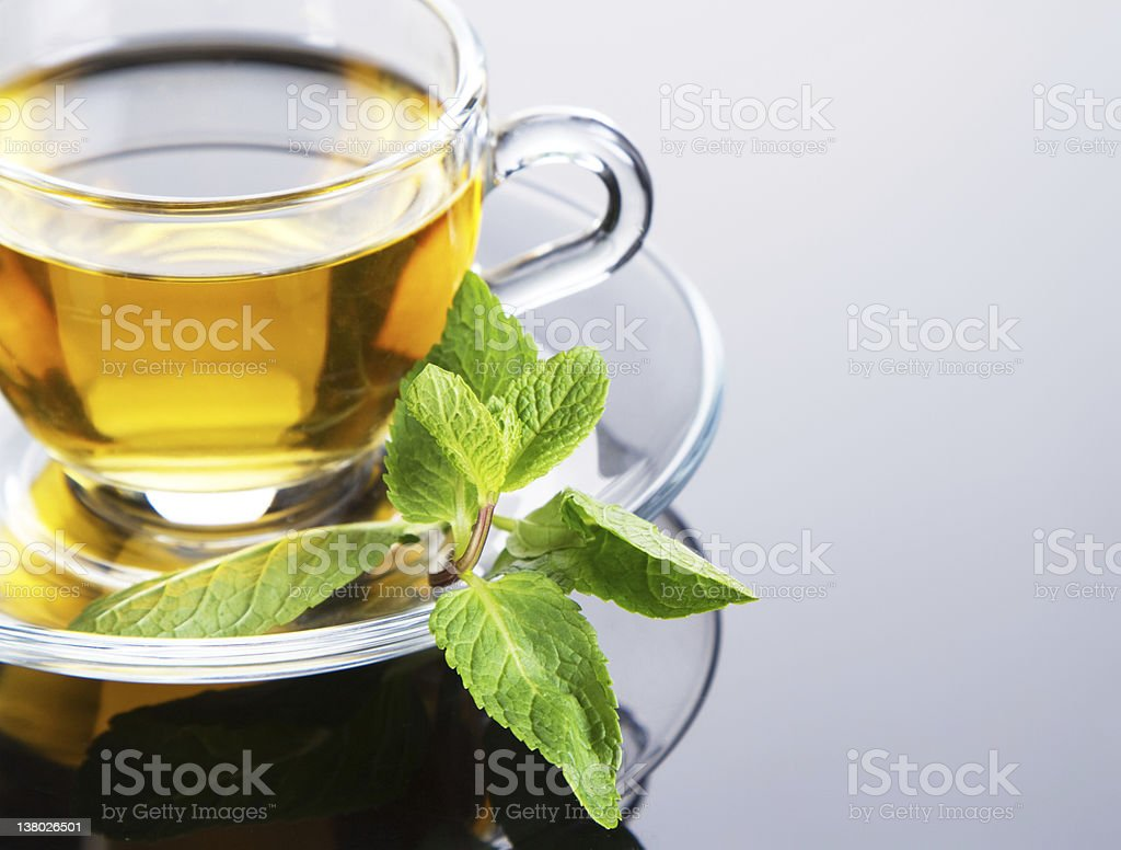 Yellow colored tea in a clear cup on saucer with fresh mint stock photo