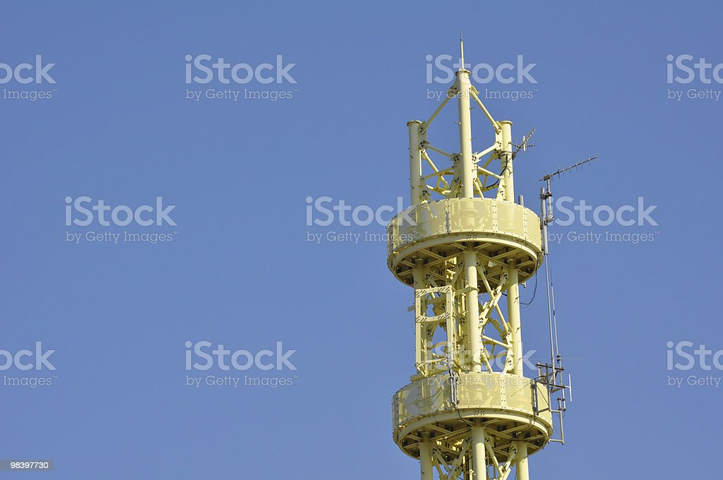Yellow communications tower against blue sky royalty-free stock photo