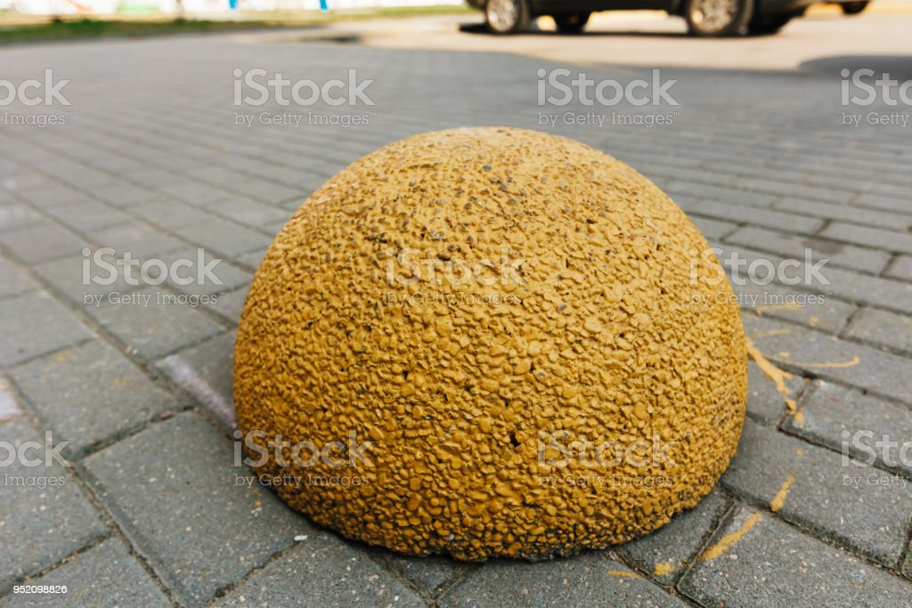 Yellow concrete hemisphere prohibiting parking barrier. Concrete limiter on road from granite pavers stock photo
