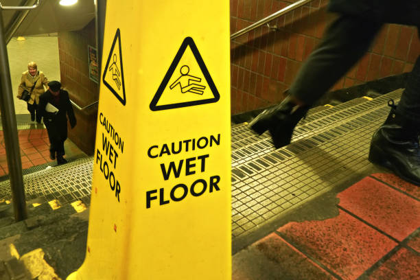 Yellow cone with caution wet floor sign on stairs to underground station stock photo