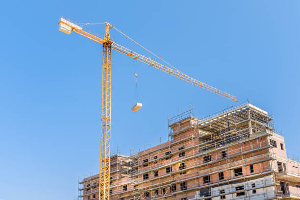 yellow constrcution crane lifts an object to a building under construction stock photo
