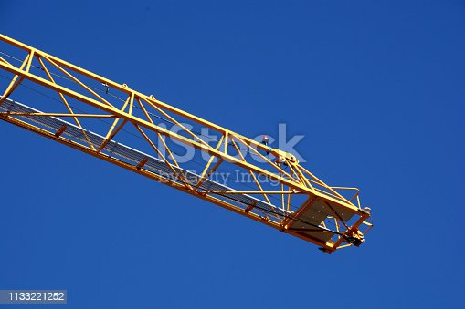 istock yellow construction tower crane arm with red warning light in front of clear blue sky 1133221252