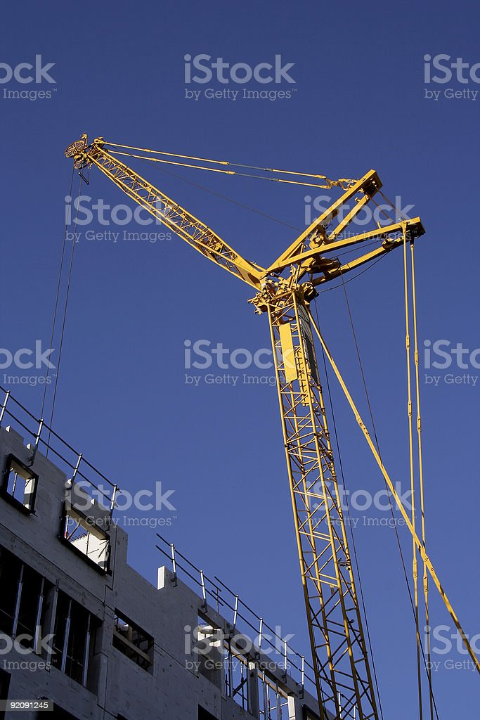 Yellow constructioncrane on a blue sky royalty-free stock photo