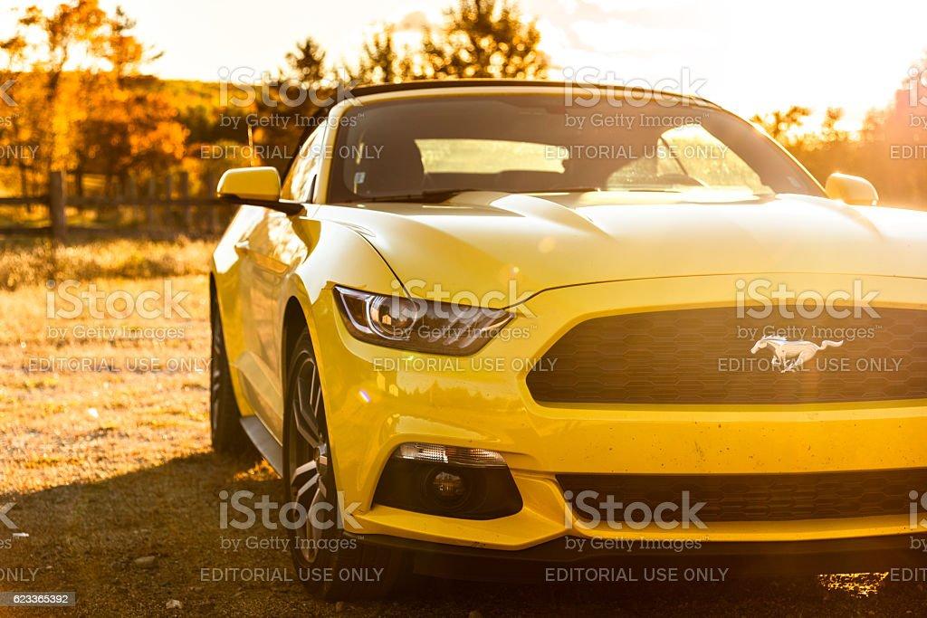 Yellow convertible mustang parked at dusk stock photo