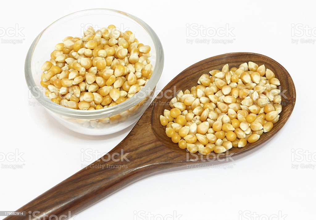 yellow corn grain and spoon isolated on white background royalty-free stock photo
