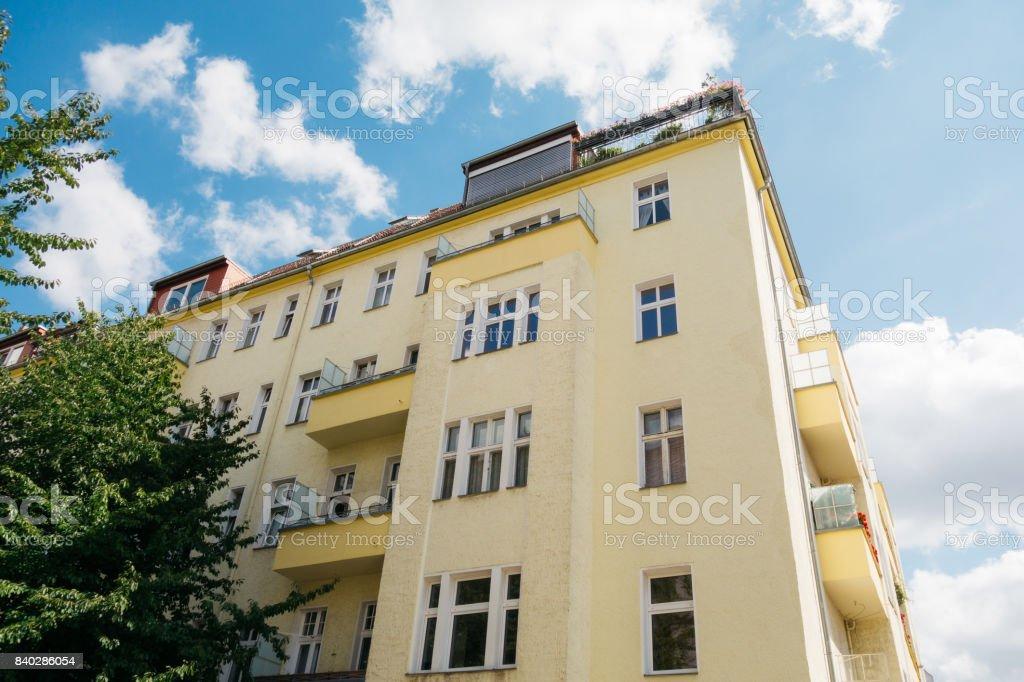 yellow corner building with green tree stock photo