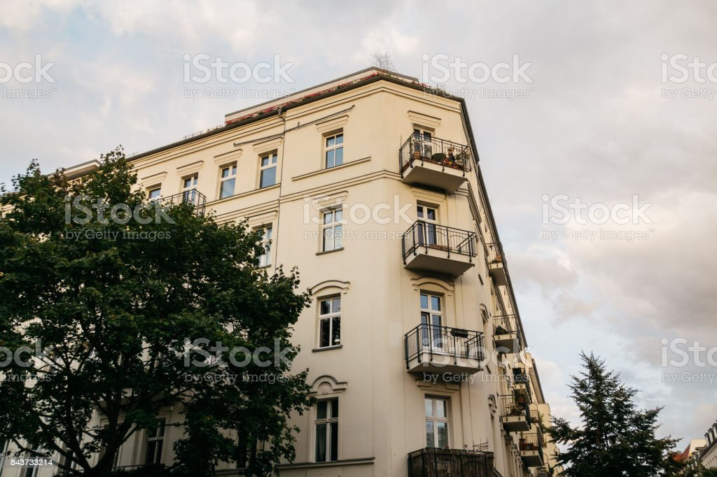 yellow corner house on cloudy day in berlin stock photo