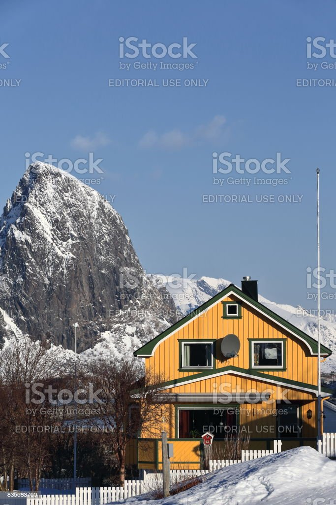 Yellow cottage-Reine village. Festhaeltinden-Akkarviktinden mounts background. Moskenesoya-Lofoten-Nordland-Norway. 0295 stock photo