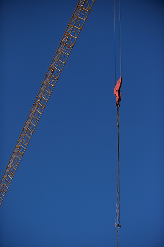 Yellow Crane Against A Clear Blue Sky Wit Red Cable Hanging Stock
