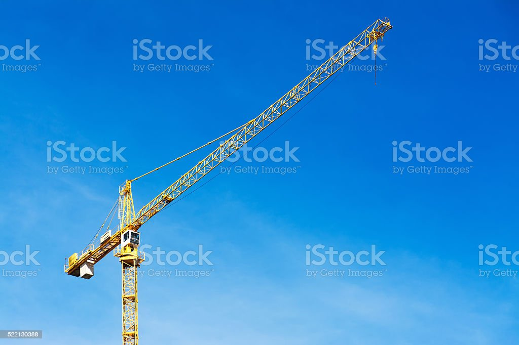 Yellow crane against blue sky stock photo