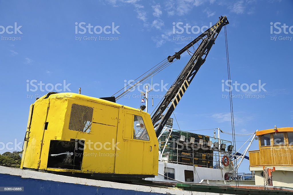 Yellow crane on Trawler stock photo