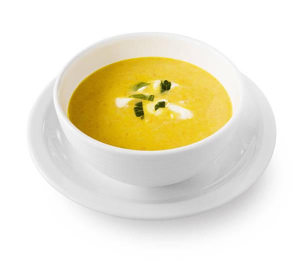 Yellow cream soup with garnish stock photo
