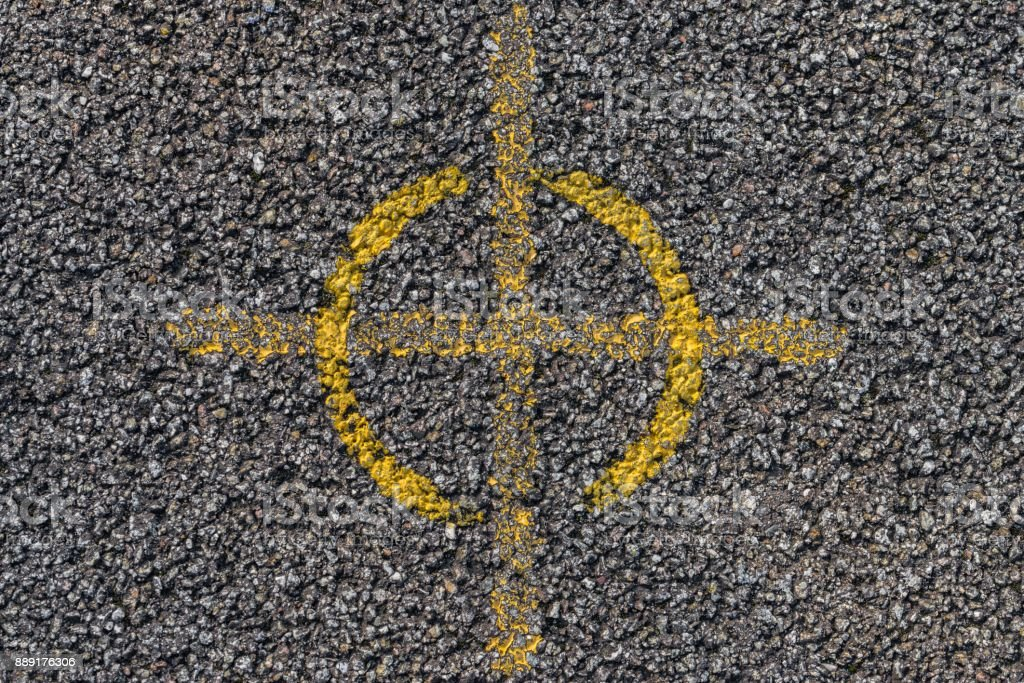 Yellow cross and ring on asphalt stock photo