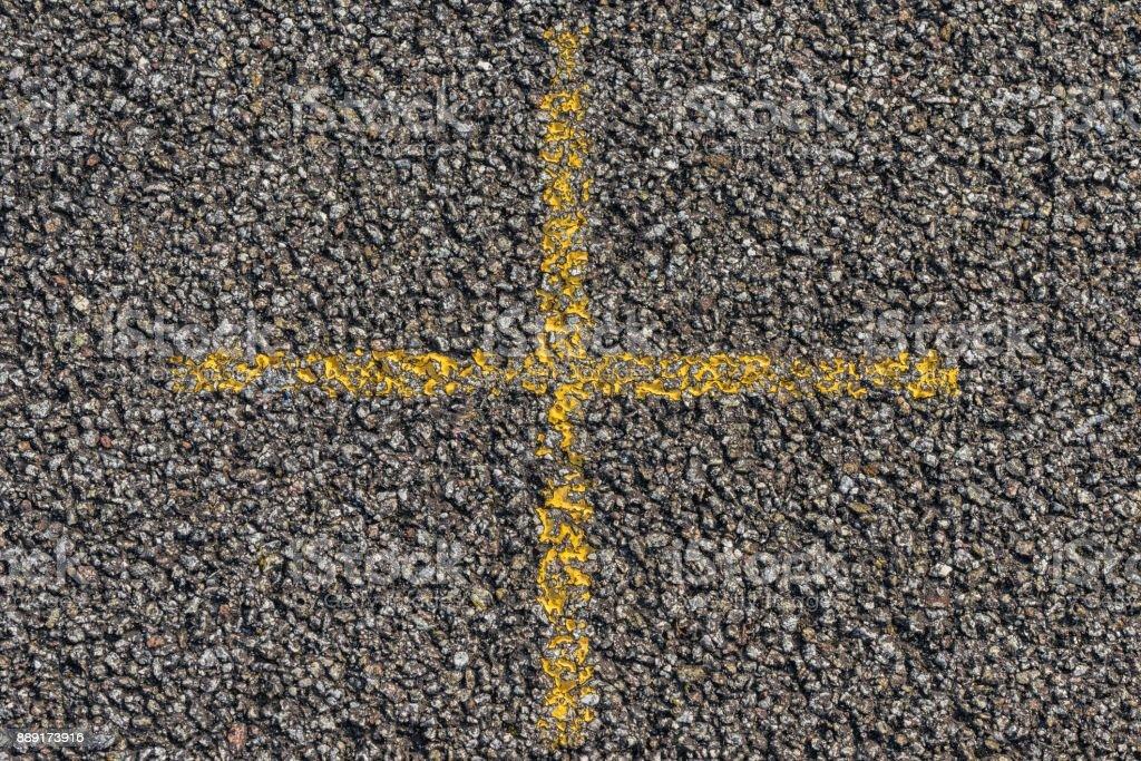 Yellow cross on asphalt stock photo