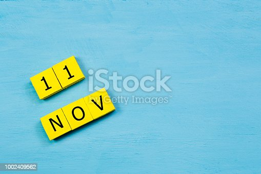 istock NOV 11, yellow cube calendar on blue wooden surface with copy space 1002409562