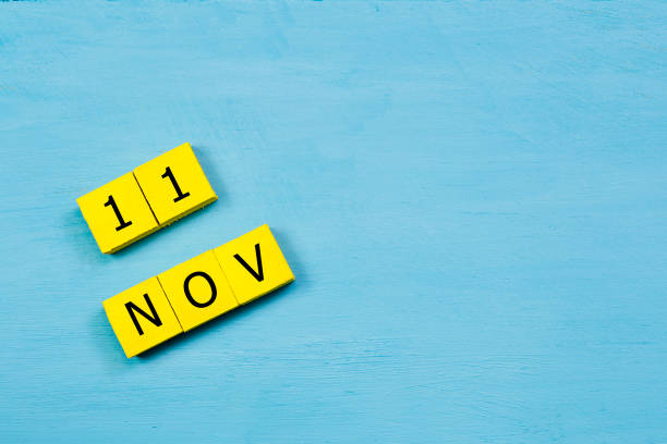 NOV 11, yellow cube calendar on blue wooden surface with copy space stock photo