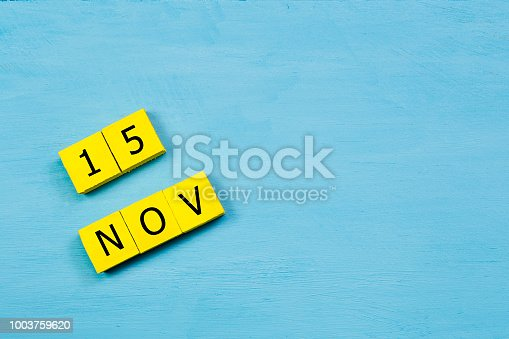 868951648 istock photo NOV 15, yellow cube calendar on blue wooden surface with copy space 1003759620