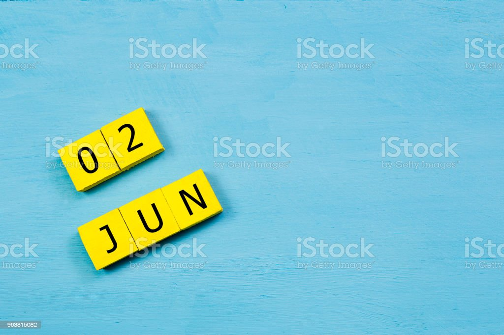 JUN 2, yellow cube calendar on blue wooden surface with copy space stock photo