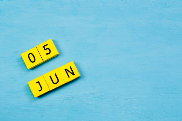 JUN 5, yellow cube calendar on blue wooden surface with copy space stock photo