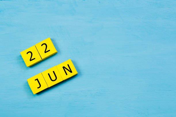 JUN 22, yellow cube calendar on blue wooden surface with copy space stock photo