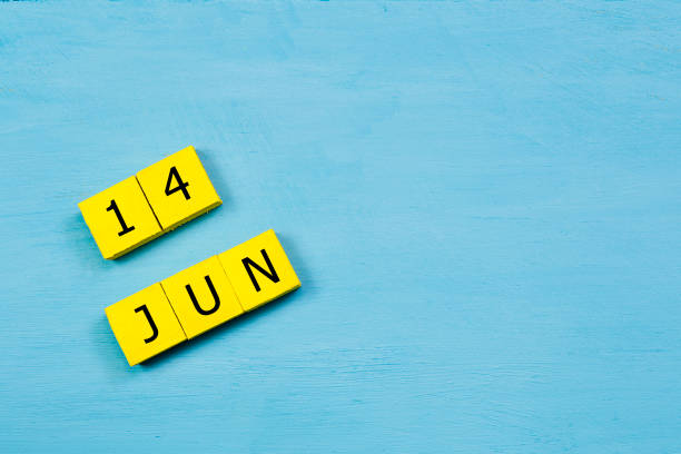 JUN 14, yellow cube calendar on blue wooden surface with copy space stock photo