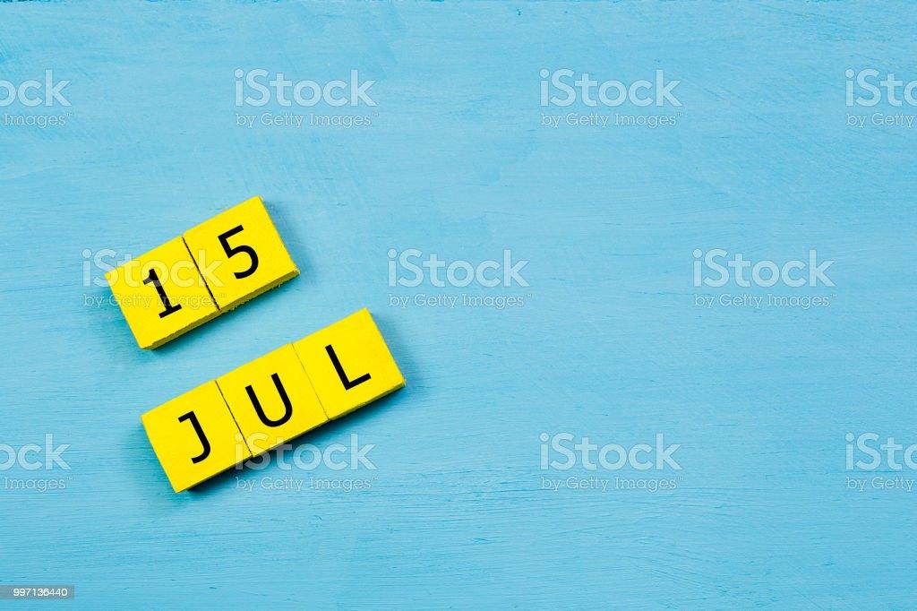 15 Temmuz, sarı küp takvim kopya alanı ile mavi ahşap yüzeyde stok fotoğrafı