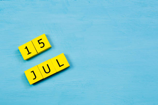 JUL 15, yellow cube calendar on blue wooden surface with copy space stock photo