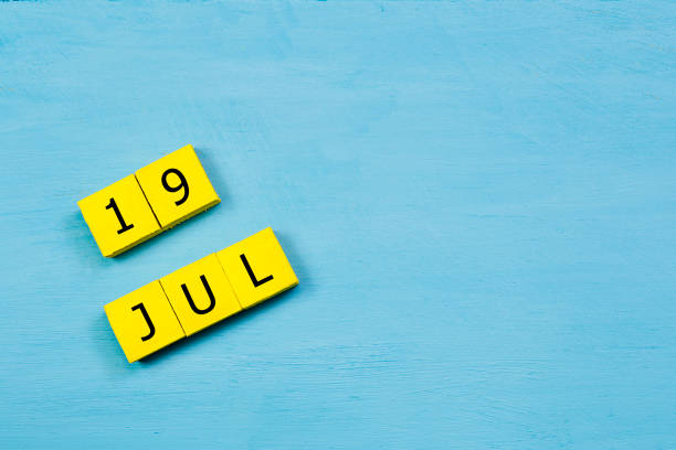 jul 19, yellow cube calendar on blue wooden surface with copy space - number 19 stock photos and pictures