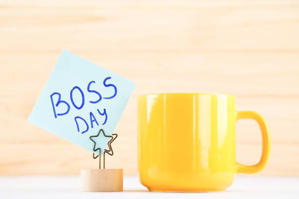 taza amarilla y pegatina con inscripción boss day sobre fondo de madera - boss's day fotografías e imágenes de stock