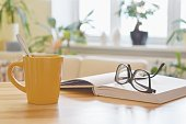 istock Yellow cup of tea, book and glasses on the table, cozy home interior background 1135791694