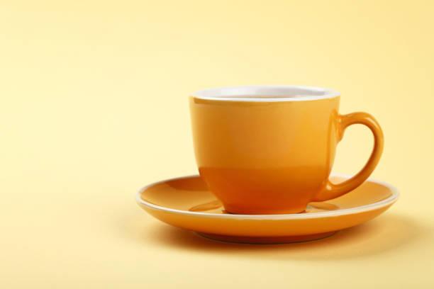 gele kopje thee of koffie op schotel - theekop stockfoto's en -beelden