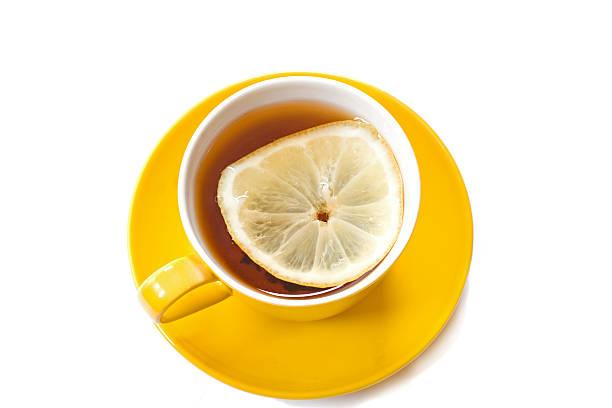 gelbe tasse mit tee und ein stück zitrone es - heiße zitrone stock-fotos und bilder