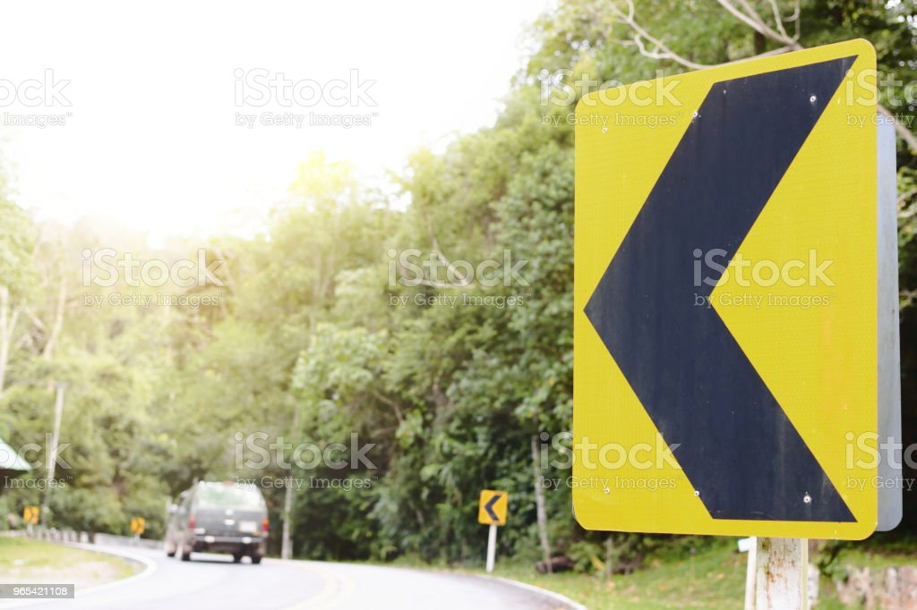 Yellow curve traffic sign on the road stock photo
